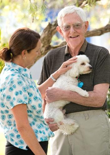 IRT carer patting an elderly mans dog
