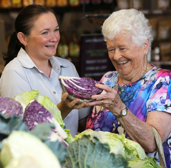 An IRT staff member assisting a home care customer with her grocery shopping