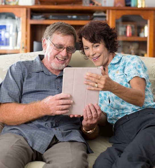 IRT home care staff member assisting older man with technology in his home