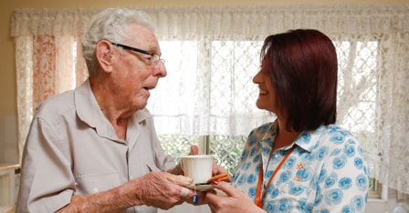 An elderly man holding a cup of tea with an IRT carer in his assisted living community