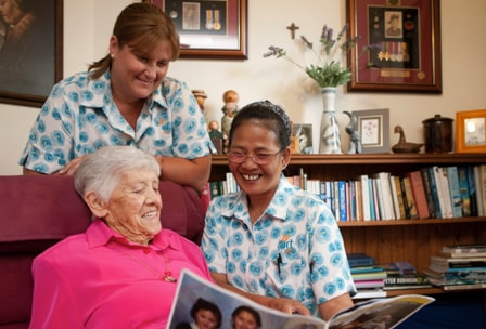 Two IRT carers looking through a photo album with an elderly woman at her home