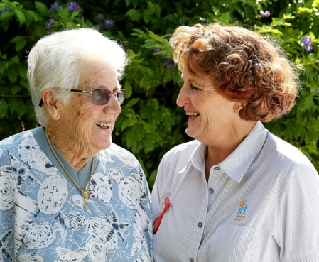 IRT carer smiling with eldery woman in retirement village