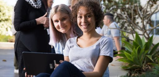 Two young women holding a tablet sitting outside