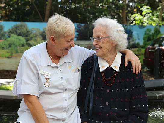 An IRT carer smiling with her arm around an elderly lady in a retirement home garden