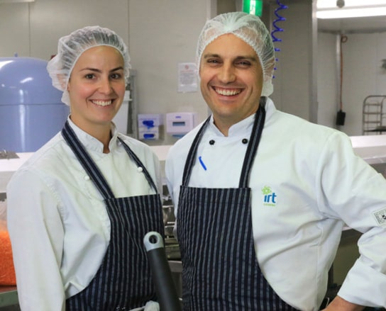 Two IRT Catering staff members smiling in the commercial kitchen